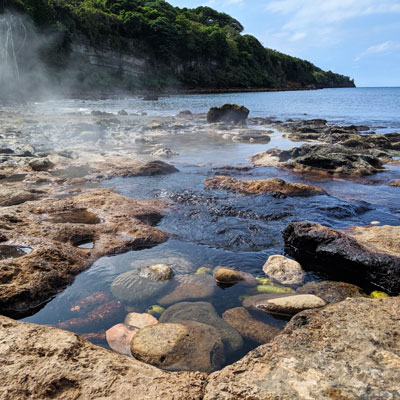 Source d'eau chaude sur une plage de sable noir à Tanna