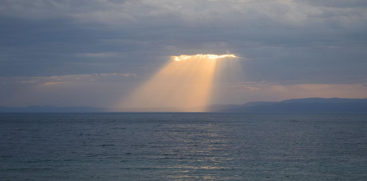 Rayons de Soleil transperçant les nuages et éclairant l'océan